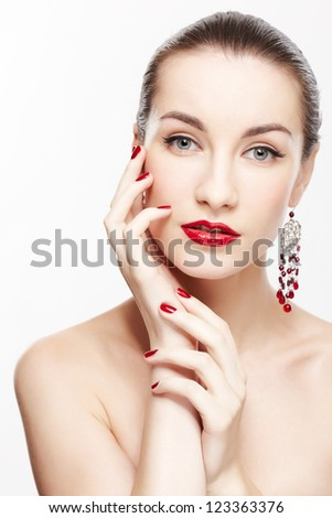 portrait of young beautiful brunette woman in jewelery touching cheek with manicured hand on gray