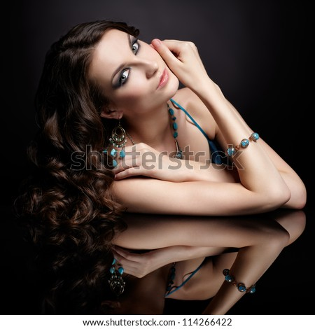 portrait of young beautiful brunette woman in jewellery at black mirror table