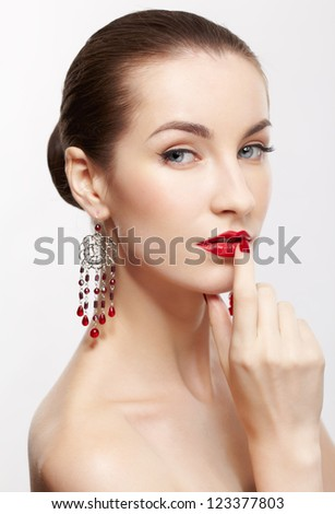 portrait of young beautiful brunette woman in jewellery on gray touching her lips with manicured finger