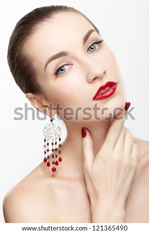 portrait of young beautiful brunette woman in jewellery on gray touching neck