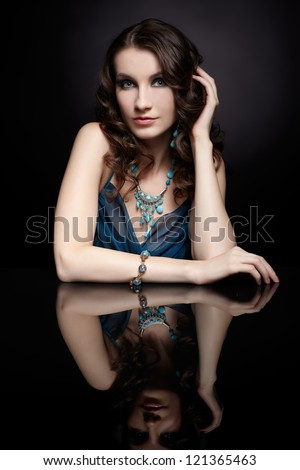 portrait of young beautiful brunette woman in jewellery sitting at black reflecting table