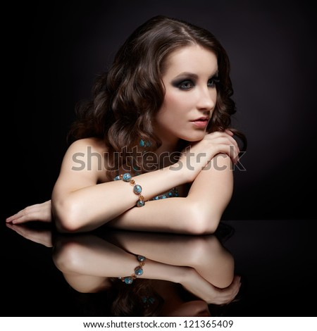 portrait of young beautiful brunette woman in jewelry at black reflecting table