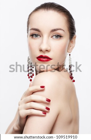 portrait of young beautiful brunette woman in jewelry touching shoulder with manicured hand