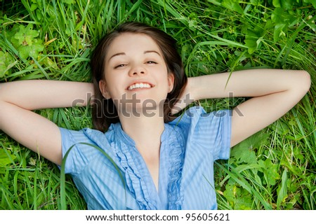 Portrait of young beautiful brunette woman lying on grass and smiling at summer park - stock photo
