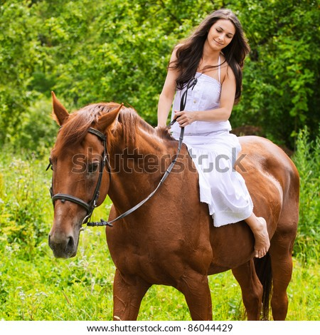 Portrait of young beautiful brunette woman wearing white dress riding dark horse at summer green forest.