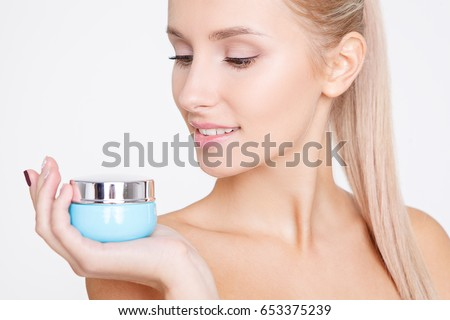 Portrait of young beautiful caucasian woman holding and looking on the cream isolated over grey background. Cleaning face, perfect skin. SPA therapy, skincare, cosmetology and plastic surgery concept #653375239