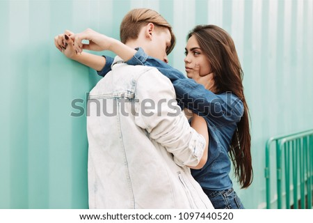 Portrait of young beautiful couple embracing each other while standing on over blue background. Pretty lady dreamily looking on her boyfriend
