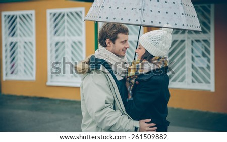Portrait of young beautiful couple embracing under the umbrella in an autumn rainy day. Love and couple relationships concept.