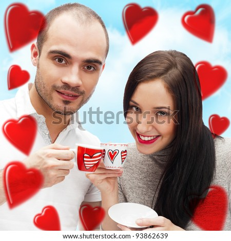 Portrait of young beautiful couple having tea or coffee beverage together at romantic background with heart shape