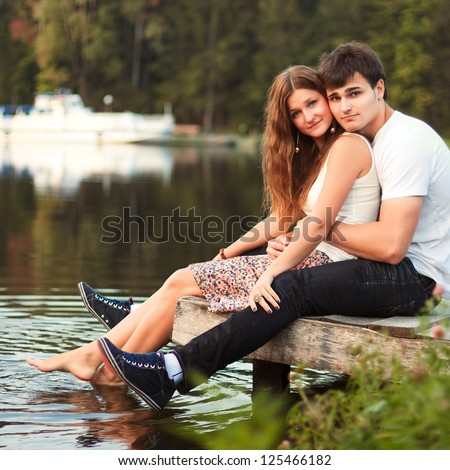 Portrait of young beautiful couple in love sitting near the water