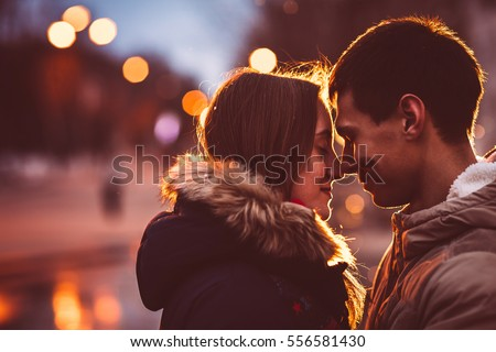 Portrait of young beautiful couple kissing in an autumn rainy day. Filtered with grain and light flashing
