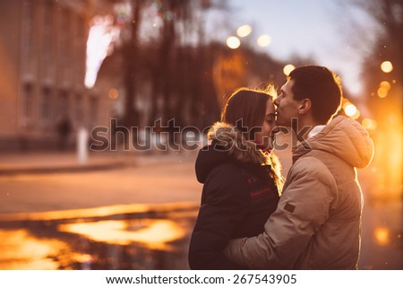 Portrait of young beautiful couple kissing in an autumn rainy day. Love  and couple relationships concept.