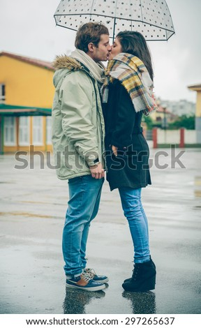 Portrait of young beautiful couple kissing under the umbrella in an autumn rainy day. Love and couple relationships concept.