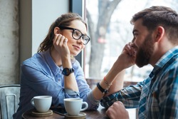 Portrait of young beautiful couple on a date drinking coffee in cafe