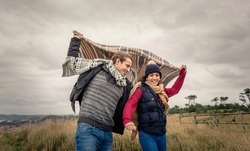 Portrait of young beautiful couple playing outdoors with blanket in a windy day over dark cloudy sky