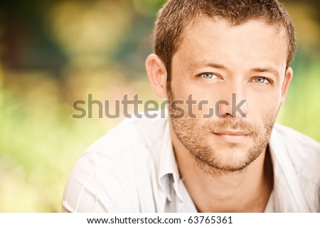 Portrait of young beautiful courageous man close up against summer garden.