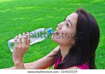 Portrait of young beautiful dark-haired woman wearing pink t-shirt drinking water at park.