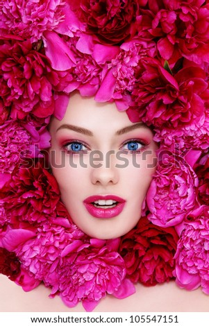 Portrait of young beautiful excited blue-eyed woman with pink peonies around her face
