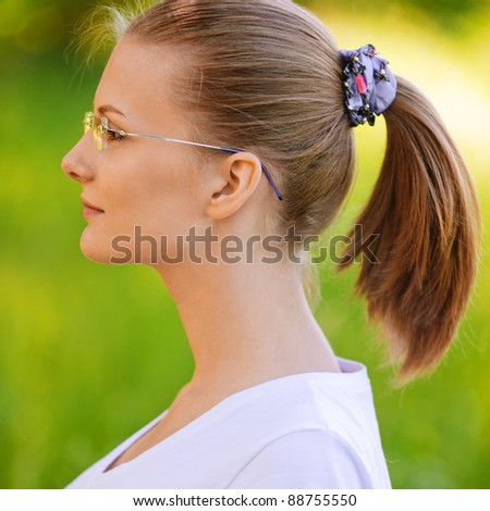 Portrait of young beautiful fair-haired woman wearing white t-shirt and eyeglasses, standing at summer green park.