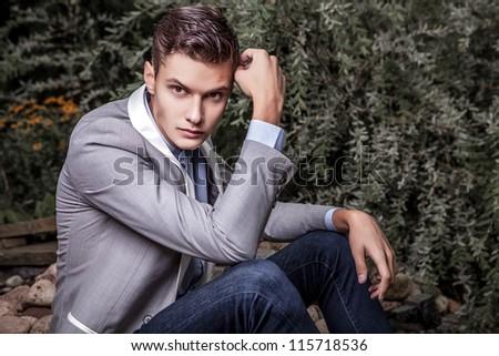 Portrait of young beautiful fashionable man against autumn garden.