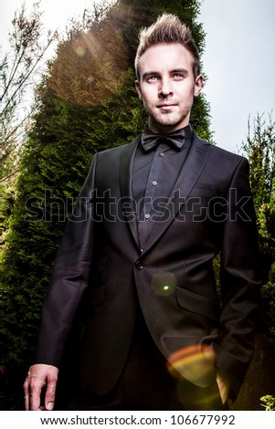 Portrait of young beautiful fashionable man against summer garden.