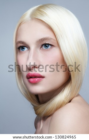 Portrait of young beautiful fresh woman with long bleached hair and clear make-up looking upwards