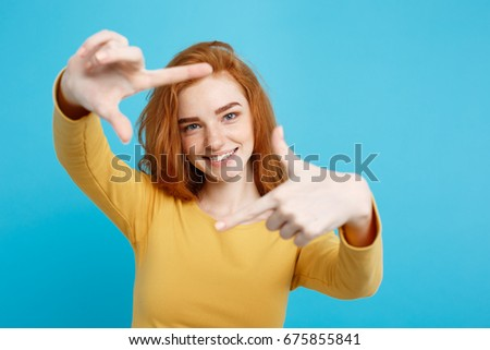 Portrait of young beautiful ginger woman with freckles cheerfuly smiling making a camera frame with fingers. Isolated on Pastel blue background. Copy space.