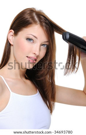 Portrait of young beautiful girl doing hairstyle with hair iron
