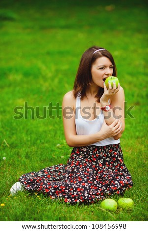portrait of young, beautiful girl holding an open book, read background summer green park
