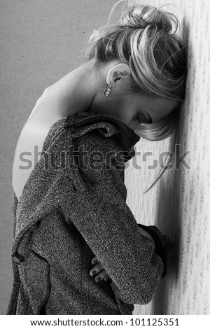 portrait of young beautiful girl in a coat longing near a wall