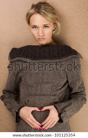 portrait of young beautiful girl in a coat on the contrary doing heart from hands
