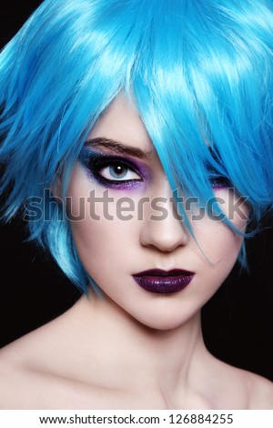 Portrait of young beautiful girl in fancy blue wig