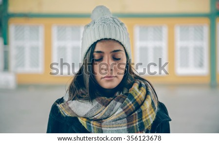 Portrait of young beautiful girl with closed eyes wearing hat and scarf in an autumn rainy day