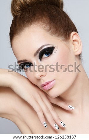Portrait of young beautiful girl with fancy cat eyes and polka dot manicure