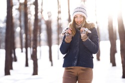 Portrait of young beautiful girl with long hair, in a blue jacket and knitted hat and mittens posing in sunny winter day. Fashion young woman in the winter forest. Christmas, winter holidays concept.