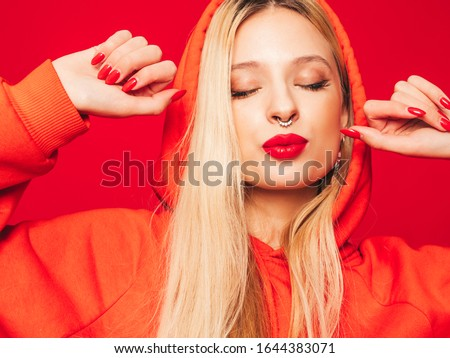 Portrait of young beautiful hipster bad girl in trendy red summer hoodie and earring in her nose.Sexy carefree smiling blond woman posing in studio.Positive model