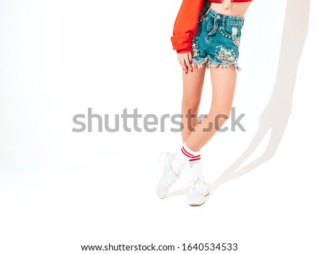 Portrait of young beautiful hipster bad girl in trendy red summer hoodie and jeans shorts.Sexy carefree blond woman posing in studio.Isolated on white