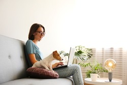 Portrait of young beautiful hipster woman working at home with her adorable jack russell terrier puppy at home in living room full of natural sunlight. Lofty interior background, close up, copy space.