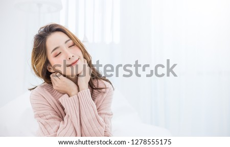 Portrait of young beautiful innocence asian woman relax in bedroom. Smile face asian girl wear winter cloth. Beauty treatment perfect clear skin japanese makeup, Asia lifestyle concept banner