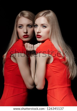 portrait of young beautiful long-haired blonde woman in red dress leaning at her reflection at mirror