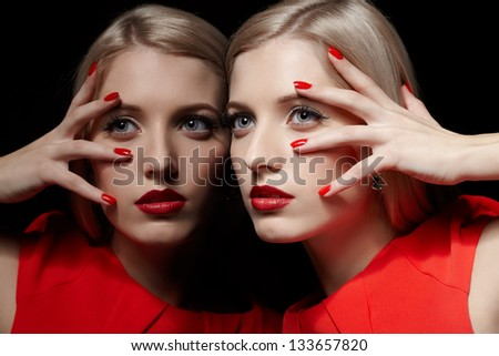 portrait of young beautiful long-haired blonde woman in red dress leaning at  mirror and touching her face with red manicured fingers