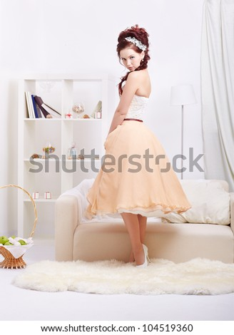 portrait of young beautiful retro woman in skirt with petticoat and corset posing in vintage interior