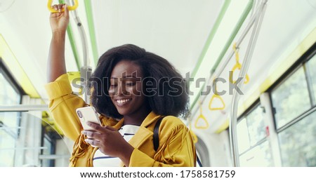Portrait of young beautiful smiling african american girl using her cell phone in public transportation.