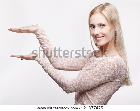 portrait of young beautiful smiling blonde woman holding small imaginary object between two hands