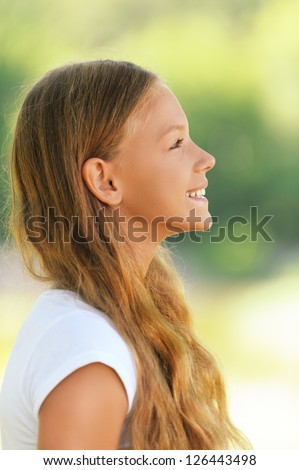 Portrait of young beautiful smiling girl in profile, against green summer garden.