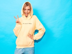 Portrait of young beautiful smiling girl in trendy summer hipster yellow hoodie.Sexy carefree woman posing near blue wall. Positive model having fun.Winks and shows peace sign