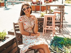 Portrait of young beautiful smiling  girl in trendy summer sundress.Sexy carefree woman sitting in veranda cafe on the street background at sunset. Positive model outdoors in sunglasses