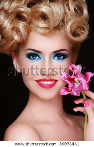 Portrait of young beautiful smiling happy blond woman with fancy make-up and flower in hand