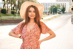 Portrait of young beautiful smiling hipster female in trendy summer sundress.Sexy carefree woman posing on the street background in hat at sunset. Positive model outdoors