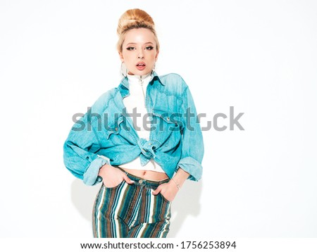 Portrait of young beautiful smiling hipster girl in trendy summer jeans jacket.Sexy carefree woman isolated on white in studio. Retro style